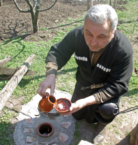 Simon Ruadze fills drinking vessel with qvevri-made wine.