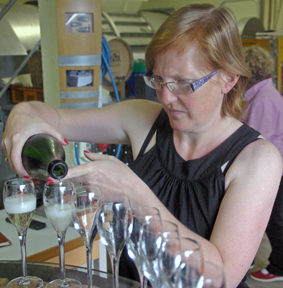 Frédérique pouring their champagne at Champagne Jean-Claude MOUZON in Verzenay