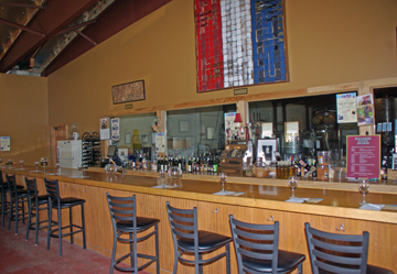 Visitors will find a large tasting room area with several antiques. Saddles make an interesting spot for visitors to have photos taken. There is plenty of room to spread out and there are tables and chairs in one section. The tasting counter is long and can accommodate a group. Wine enthusiasts sit at the tasting counter. Behind the tasting counter, windows provide a glimpse into the winery. Founders Wine Cellar